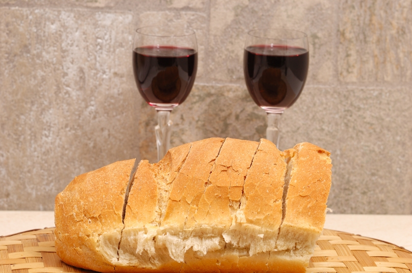 slices of bread and two glasses of wine in background